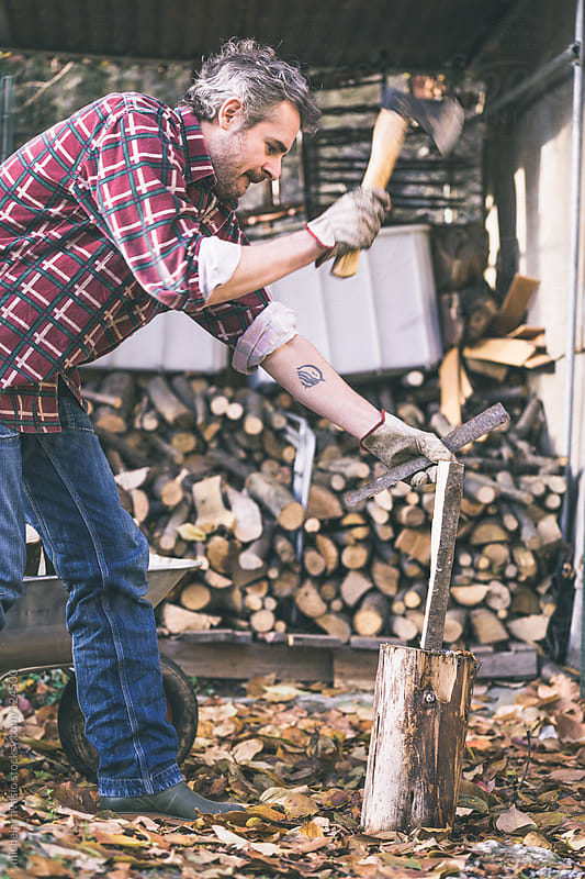 Man cutting firewood with ax by michela ravasio for Stocksy United