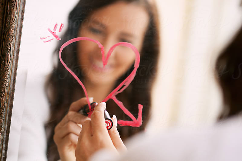 Valentine's: Woman Drawing Heart On Bathroom Mirror In Lipstick by Sean Locke for Stocksy United