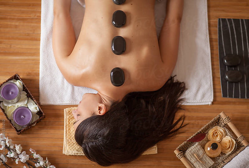 Client Enjoying Hot Stone Ritual in Spa Center by Mosuno for Stocksy United