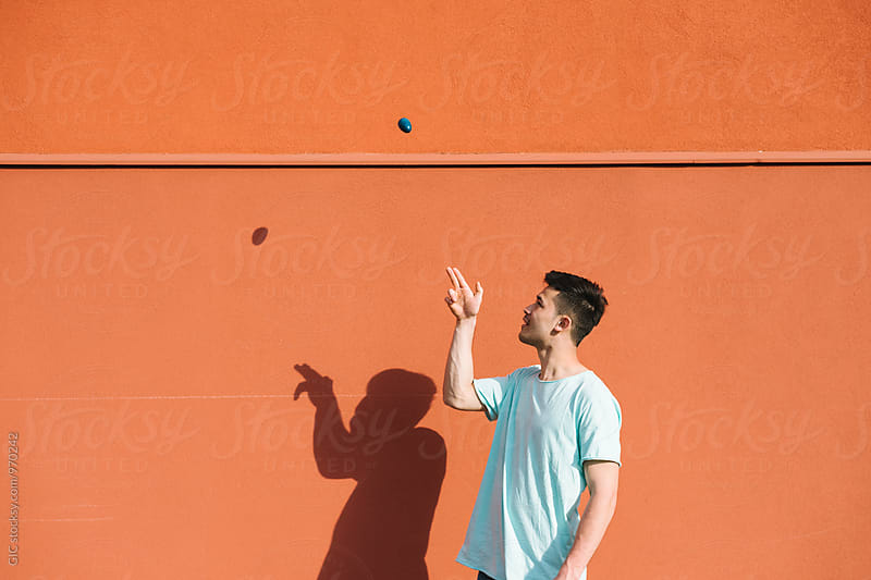 Man playing with a blue egg by Simone Becchetti for Stocksy United