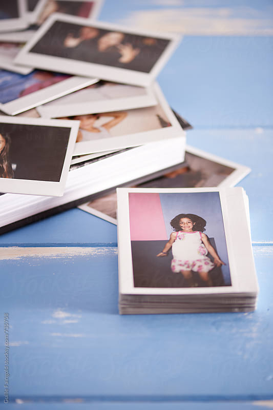 bunch of polaroids and book on a blue wooden table by Guille Faingold for Stocksy United