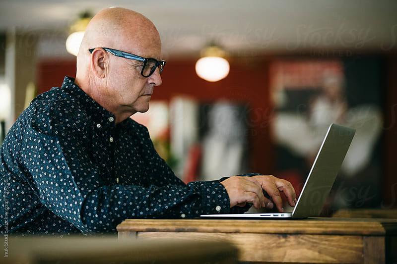 Stylish senior businessman, working in a cafe restaurant on his laptop by Inuk Studio for Stocksy United