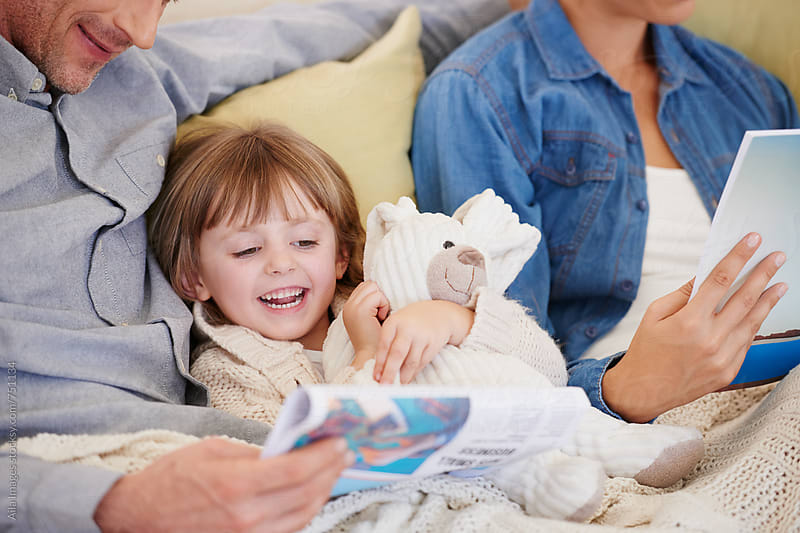 Family together at home relaxing on the sofa by Aila Images for Stocksy United