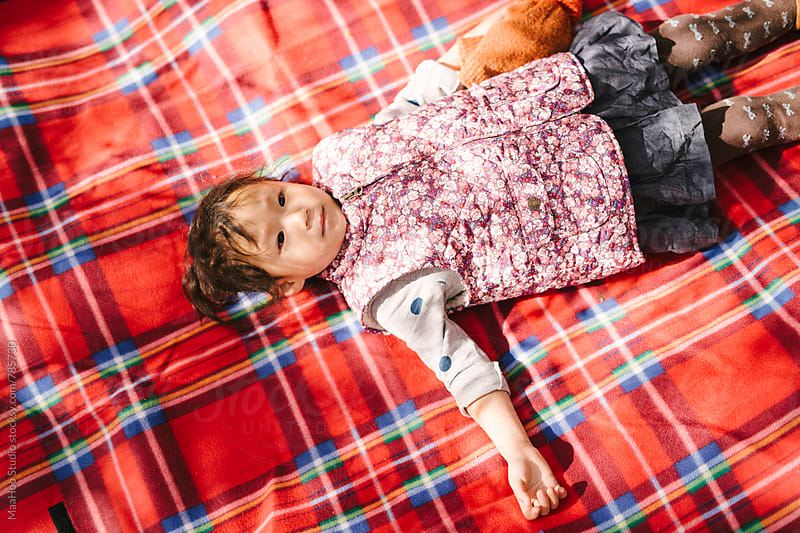 Cute toddler girl lying on picnic mat by Maa Hoo for Stocksy United