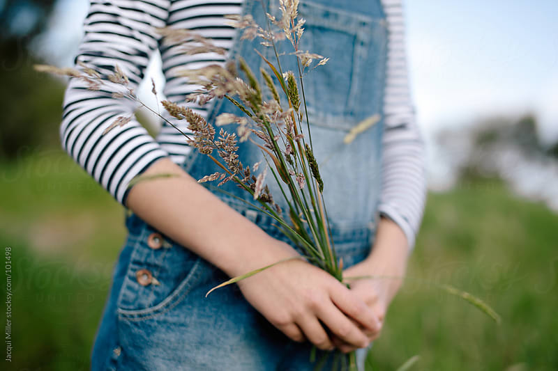 Girl holding long flowering grass in her hands  by Jacqui Miller for Stocksy United