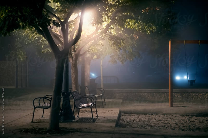 Benches and trees in a foggy park at night with car headlights in the distance by Rachel Bellinsky for Stocksy United