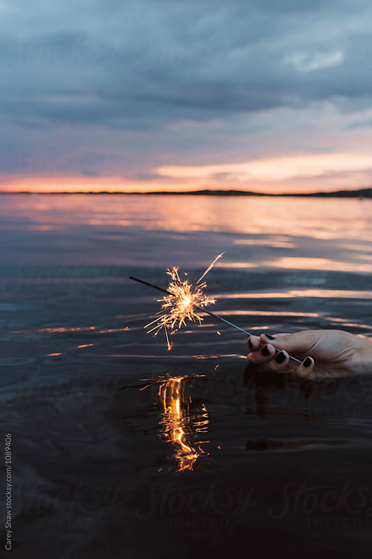 Young woman in lake holding sparklers against water by Carey Shaw for Stocksy United