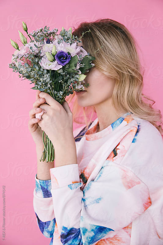 Close-up of blonde woman hiding face with bouquet of wildflowers by Danil Nevsky for Stocksy United