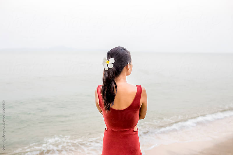 Beautiful asian girl on beach looking at the sea with flower in her hair by Søren Egeberg Photography for Stocksy United
