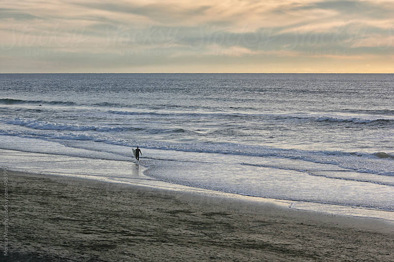 Lone surfer walks into ocean with his surf board by Monica Murphy for Stocksy United