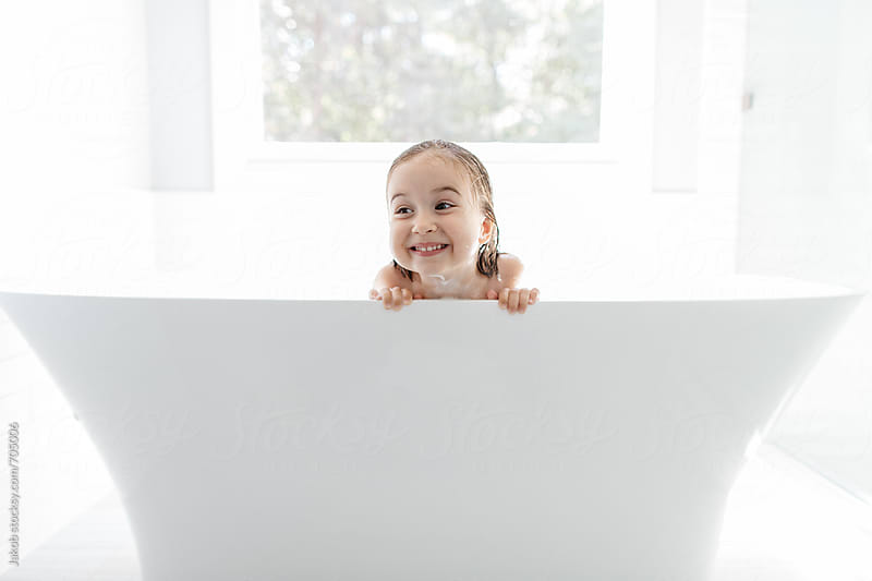 Cute young girl peeking out from a big bathtub by Jakob for Stocksy United