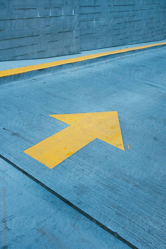 Orange directional  arrow on urban street by Paul Edmondson for Stocksy United