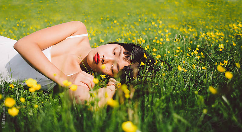 Beautiful young asian woman sleeping in the spring field with yellow flower under the sun by Nabi Tang for Stocksy United