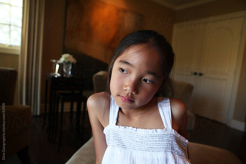 Asian girl sitting in bedroom showing wide angle view contemplative expression by Dina Giangregorio for Stocksy United