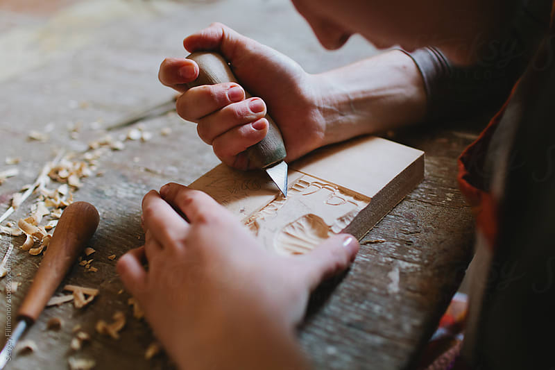 Woman carpenter carves a wooden stamp by Sergey Filimonov for Stocksy United