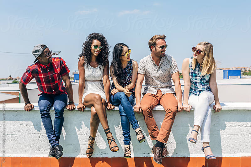 Group of Multi-Ethnic Friends Hanging out in a Rooftop by Victor Torres for Stocksy United