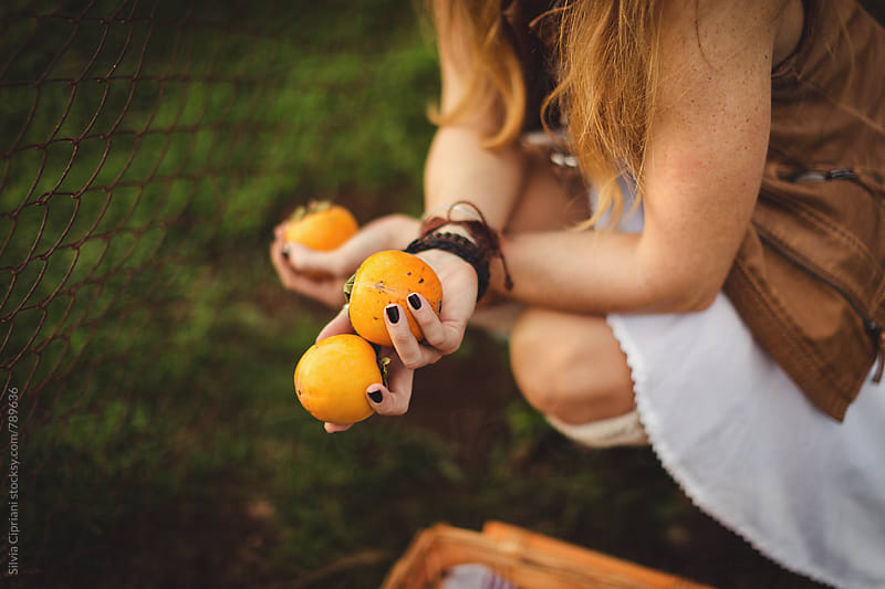 Woman holding fresh kaki fruit in hands by Silvia Cipriani for Stocksy United