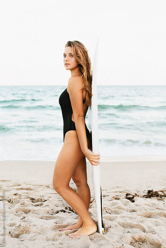 Girl standing against a surf board by Ellie Baygulov for Stocksy United