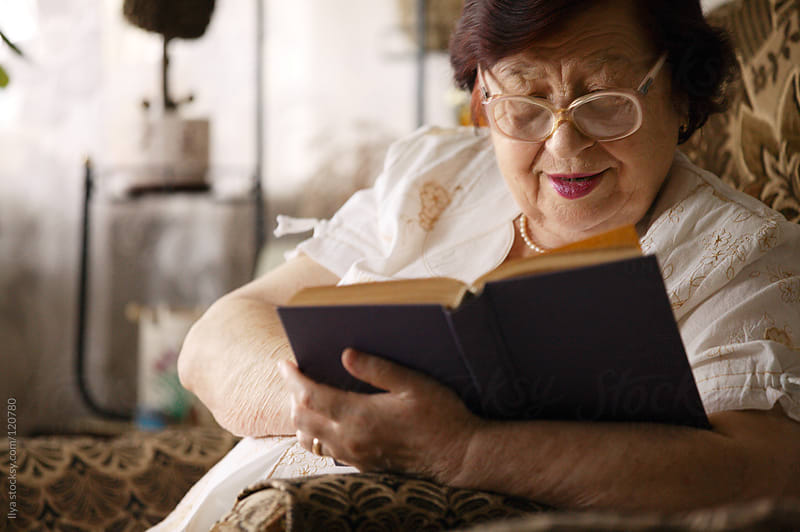 Senior woman reading a book by Ilya for Stocksy United