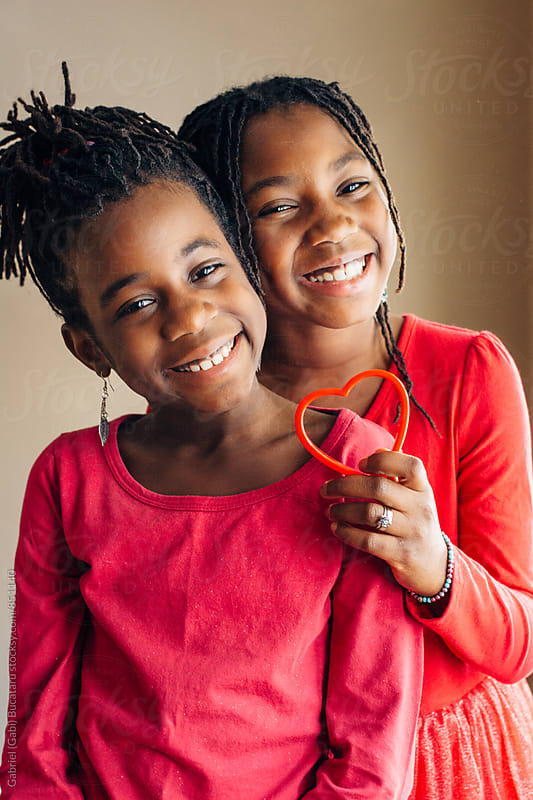 Smiling black girls in red by Gabriel (Gabi) Bucataru for Stocksy United