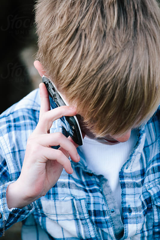 Trendy teenage boy on his mobile phone by Helen Rushbrook for Stocksy United