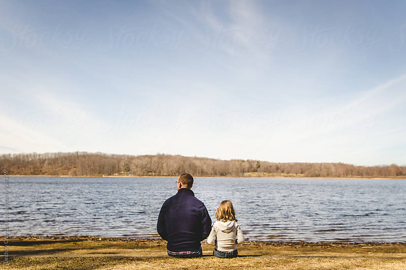 Man and girl sitting together by a body of water by Lindsay Crandall for Stocksy United