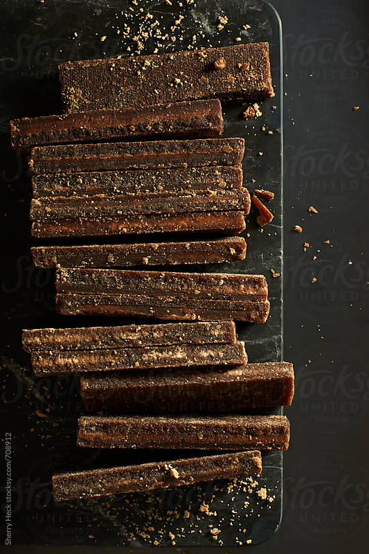 Bars of brown sugar and sugar granules on dark marble surface by Sherry Heck for Stocksy United
