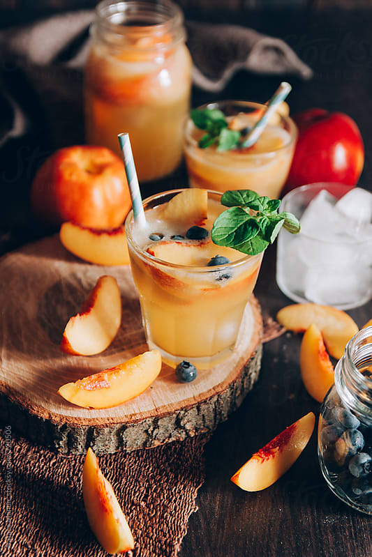 Fresh peach cocktail with blueberries and mint by Nataša Mandić for Stocksy United