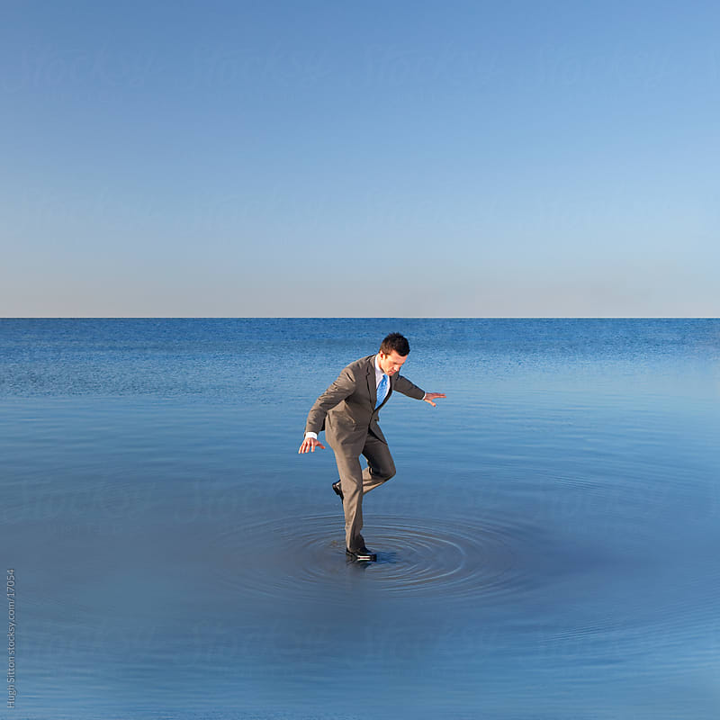 Businessman balancing on water. by Hugh Sitton for Stocksy United