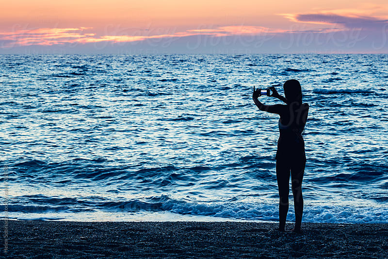 Young Woman at the Beach Takes a Picture of the Sunset with a Mobile Phone by Helen Sotiriadis for Stocksy United
