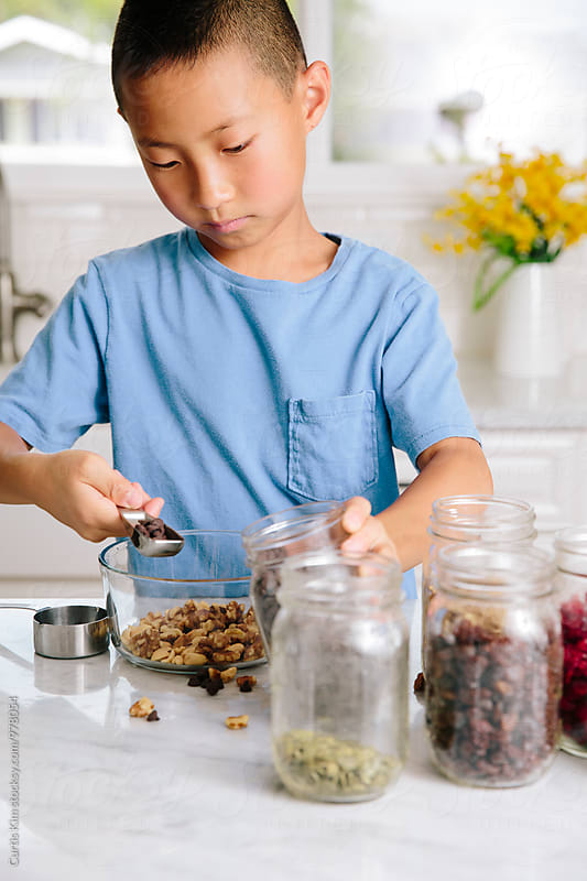 Asian boy preparing a healthy snack by Curtis Kim for Stocksy United