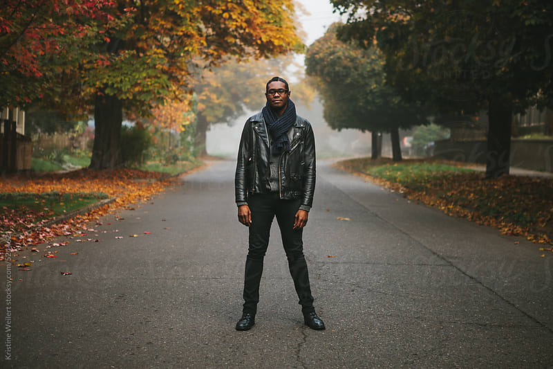 Portrait of a man standing in the street with autumn colored trees by Kristine Weilert for Stocksy United