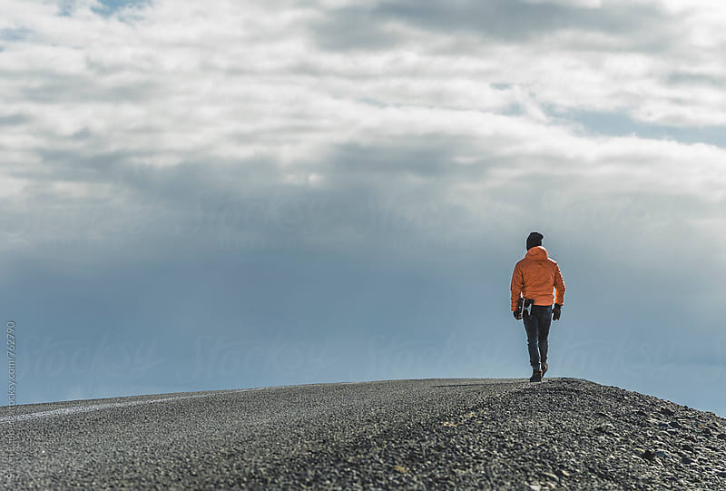Man walking away carrying skateboard in Iceland by Søren Egeberg Photography for Stocksy United