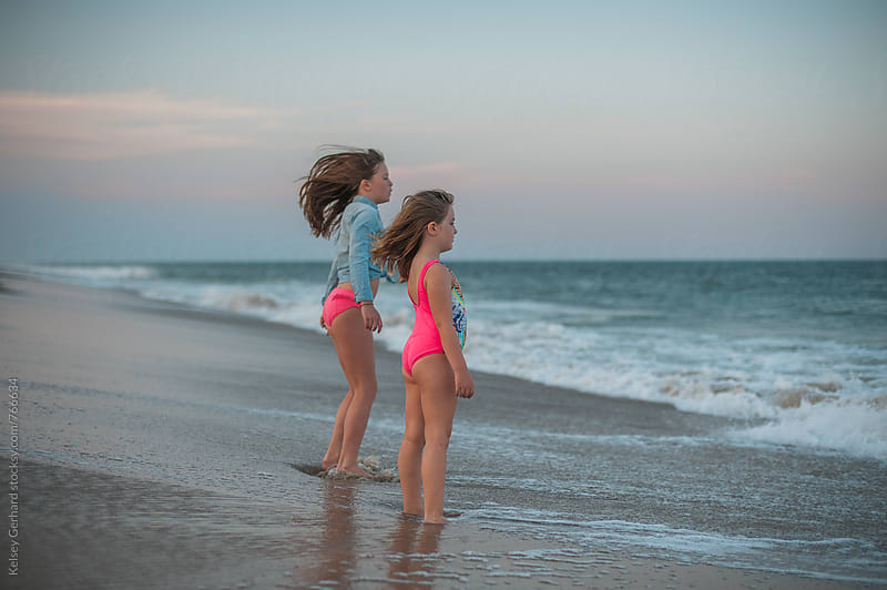 Sisters look out at the ocean at sunset. by Kelsey Gerhard for Stocksy United