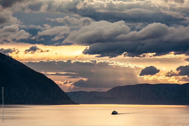 A single boat in the ocean in the Norwegian fjords during a golden sunset by Cindy Prins for Stocksy United