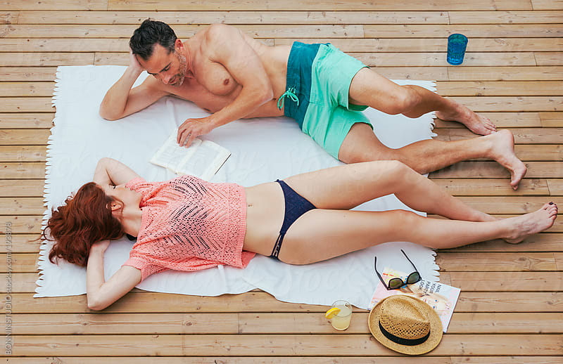 Aerial view of beautiful couple sunbathing on a wooden terrace. Summer time. by BONNINSTUDIO for Stocksy United