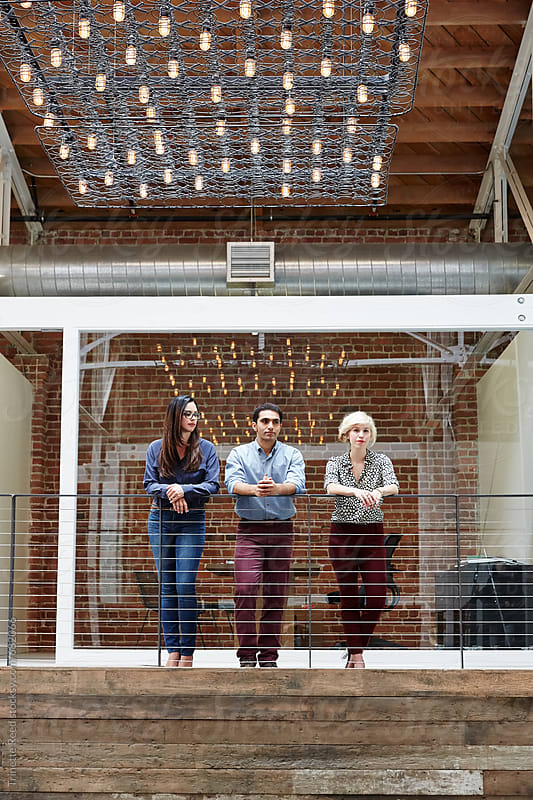 Group portrait of millennials standing in loft office space by Trinette Reed for Stocksy United