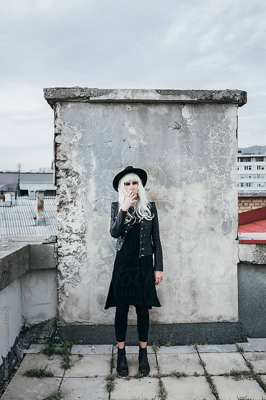 Alternative androgen model with grey hair on a rooftop by Maja Topcagic for Stocksy United