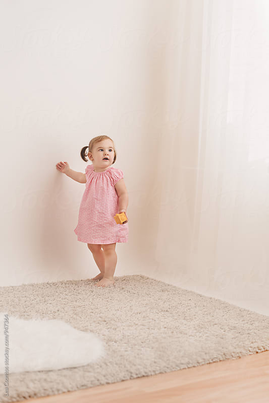 Cute little girl standing in a room with a curious look on her face by Lea Csontos for Stocksy United