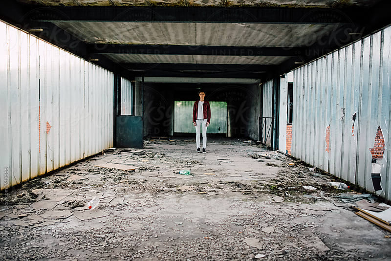 Attractive woman standing in the abandoned factory  by Boris Jovanovic for Stocksy United