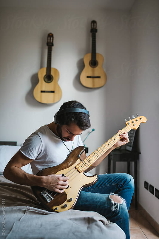 Young man playing bass guitar at home by GIC for Stocksy United