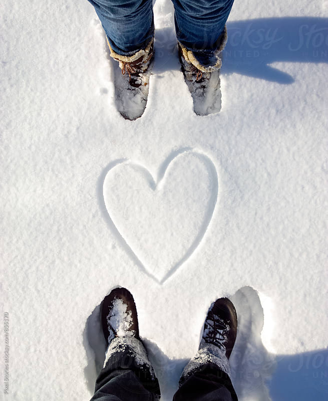 Two people with snow heart between them by Pixel Stories for Stocksy United