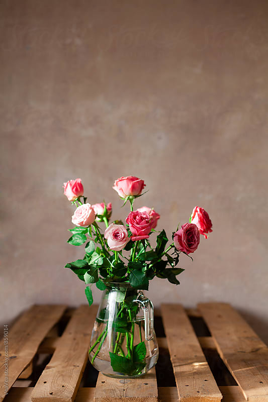 Bouquet of roses in a glass vase on the table  by Marija Mandic for Stocksy United