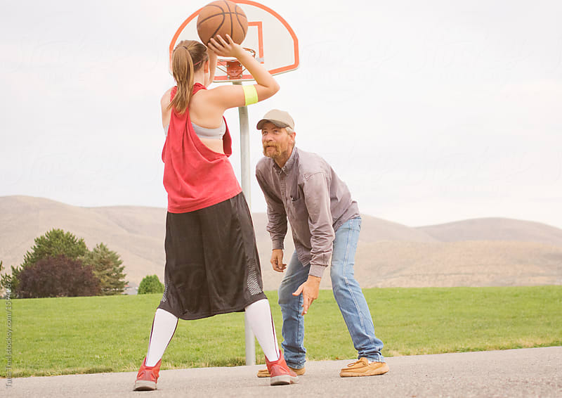 A daughter attempts a shot while playing basketball with her father by Tana Teel for Stocksy United