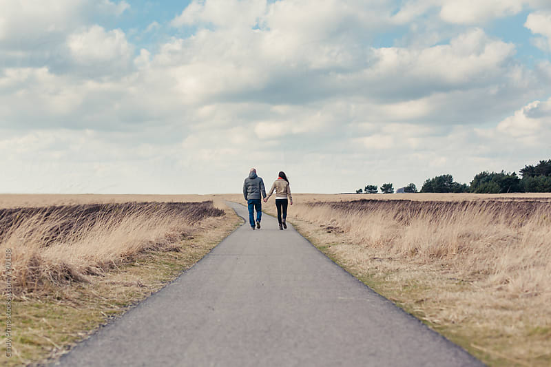 Couple holding hands and walking away on a path in a field on a beautiful winter day by Cindy Prins for Stocksy United
