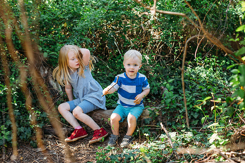 A little Girl rubs her head in pain while little brother holds a stick gleefully by Amanda Voelker for Stocksy United