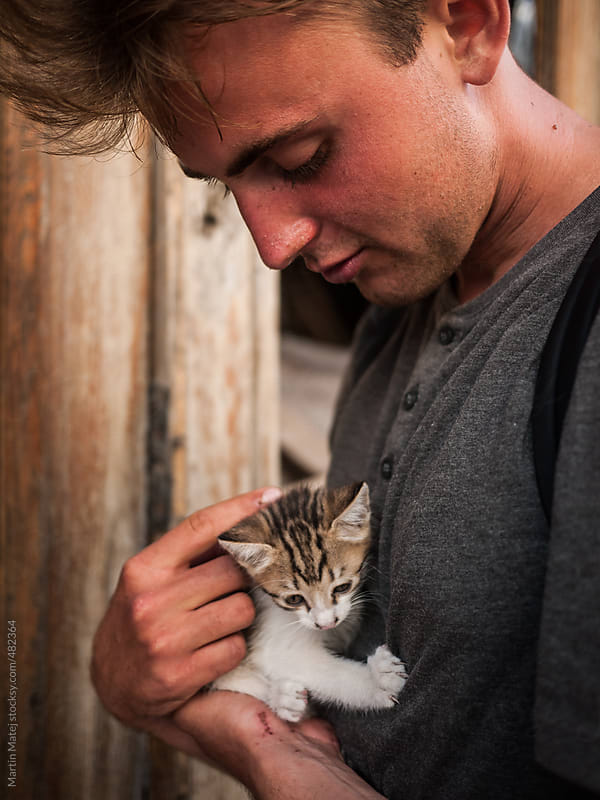 Young man petting and hugging abandoned kitty by Martin Matej for Stocksy United