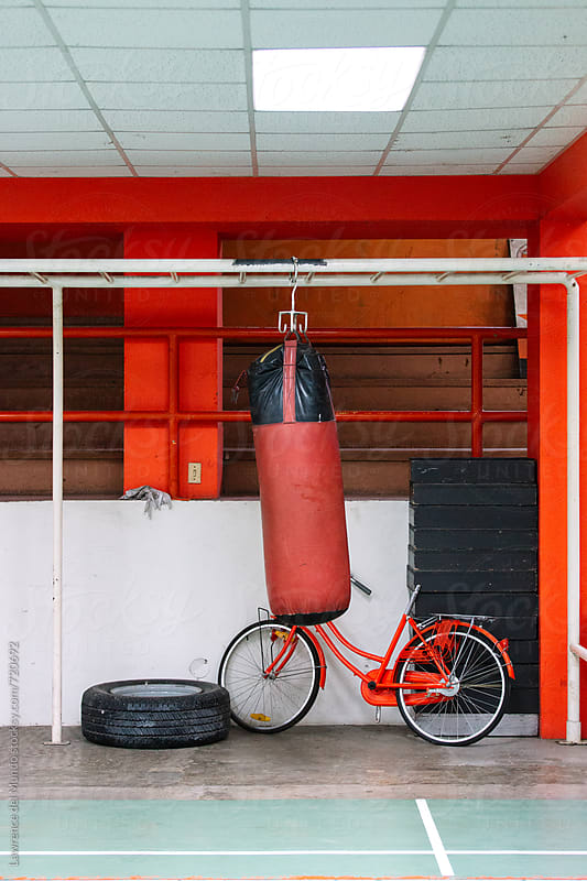 Contents of a spartan gym: a tire with rim, a punching bag, and bicycle with no seat. :D by Lawrence del Mundo for Stocksy United