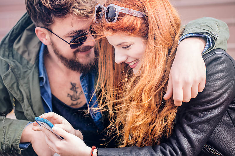 Young Couple With a Mobile Phone by Lumina for Stocksy United