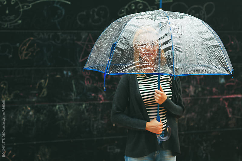 Portrait of a blonde woman holding an umbrella under the rain.  by BONNINSTUDIO for Stocksy United
